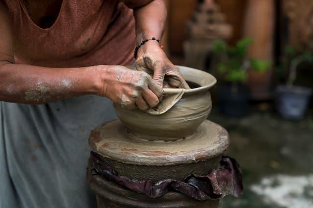 Senhora moldando vaso de barro