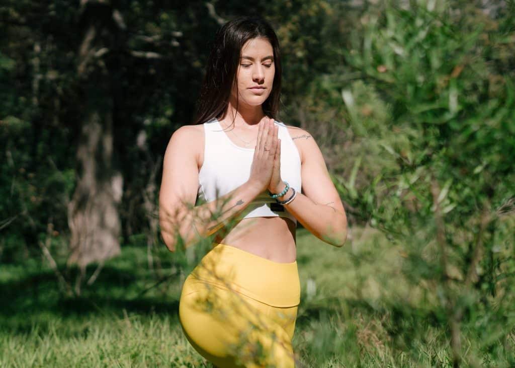 Mulher em pé, com roupas de ginástica, rezando em um parque.