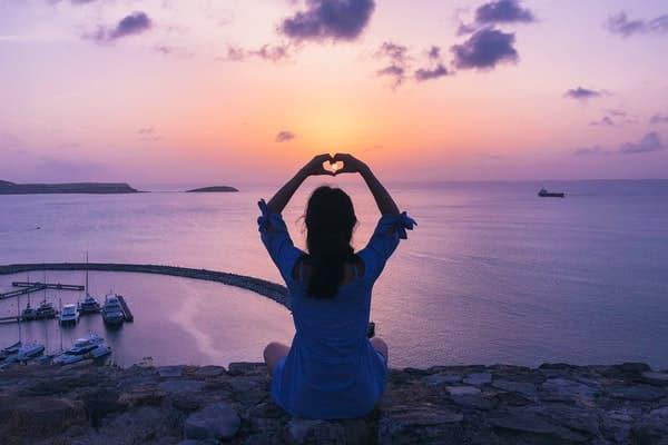 Mulher sentada de costas com mãos para o alto fazendo coração com mar e pôr-do-sol ao fundo