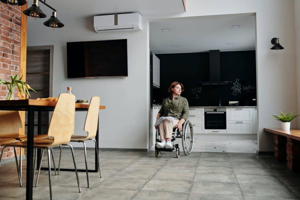 Mulher em uma cadeira de rodas sozinha em sua casa.
