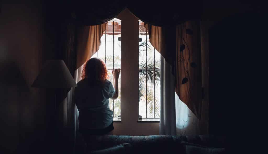 Silhueta de uma mulher olhando pela janela.