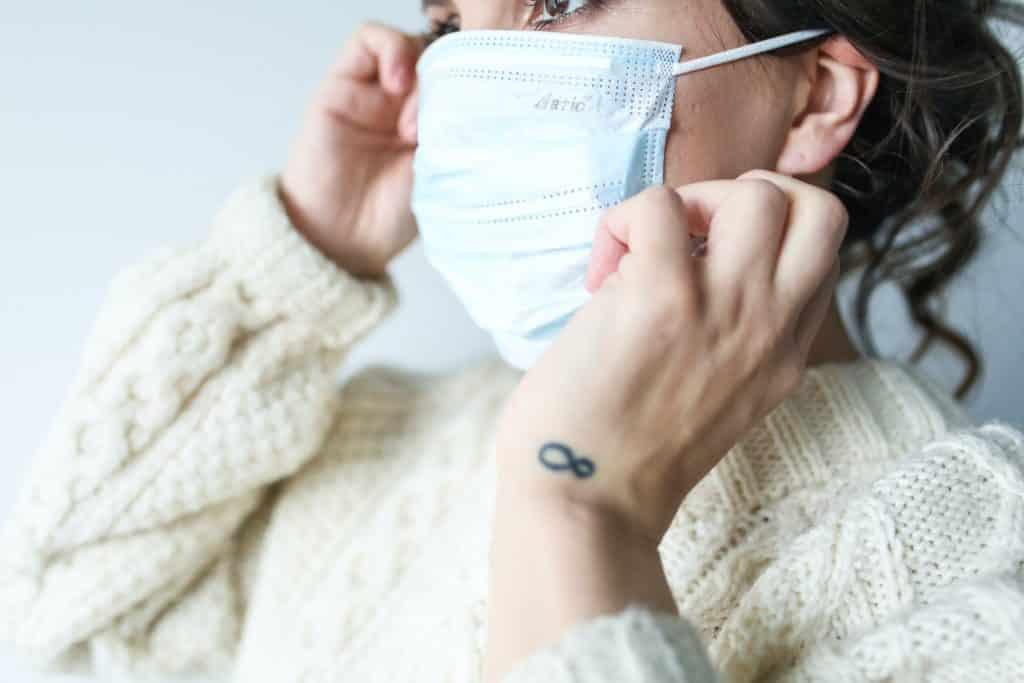 Mulher ajustando sua máscara de proteção facial com as mãos.