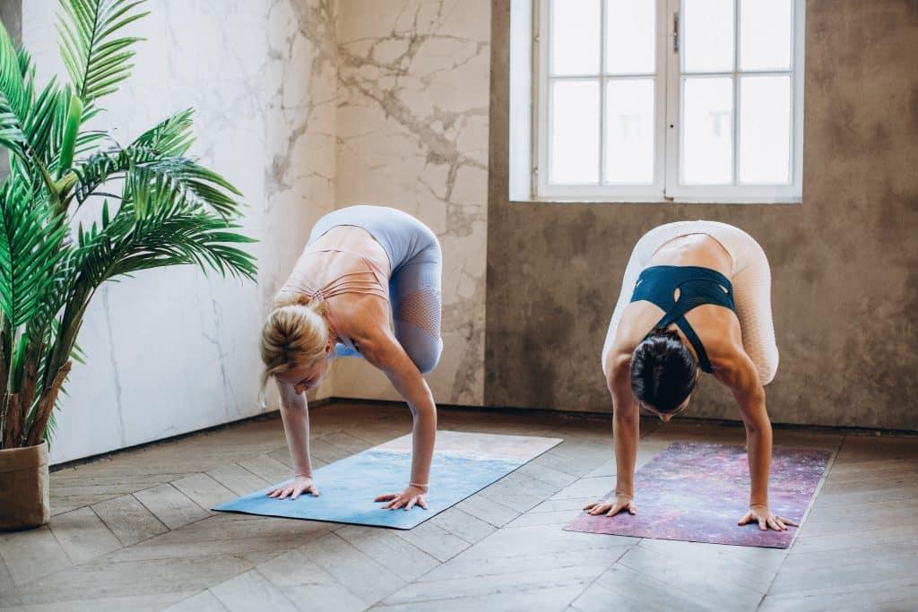 Duas mulheres praticando yoga na pose Bakasana.