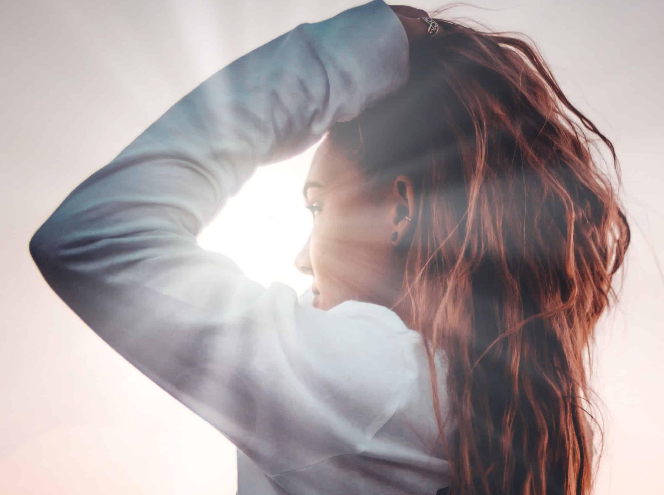 Garota de perfil mexendo no cabelo com brilho refletindo