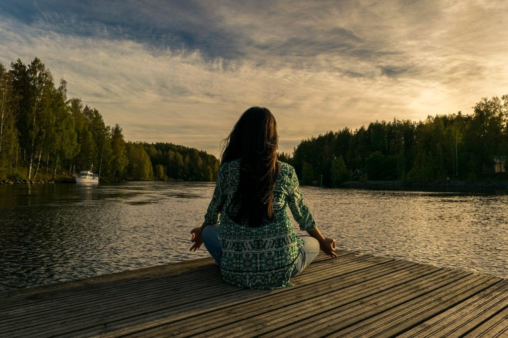 Mulher sentada em pier, de frente para um grande rio, meditando.