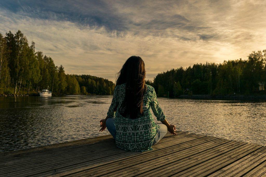Imagem de uma mulher sentada em um pier de frente para um lago. Ela está sentada de costas em posição d meditação.