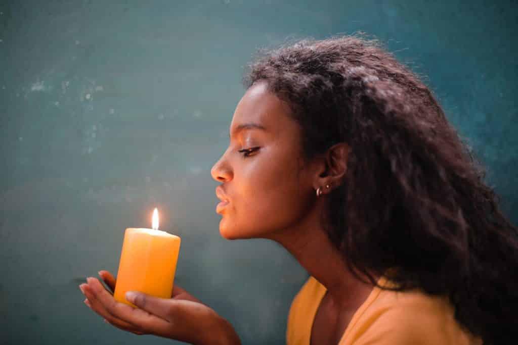 Mulher vista de perfil assoprando uma vela.