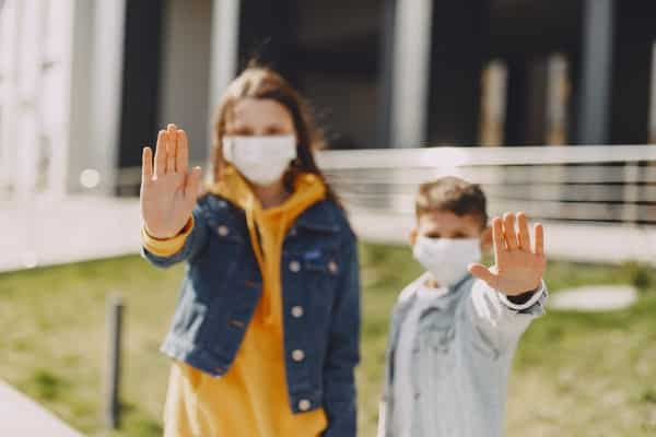 Crianças com máscara e mãos em frente ao corpo
