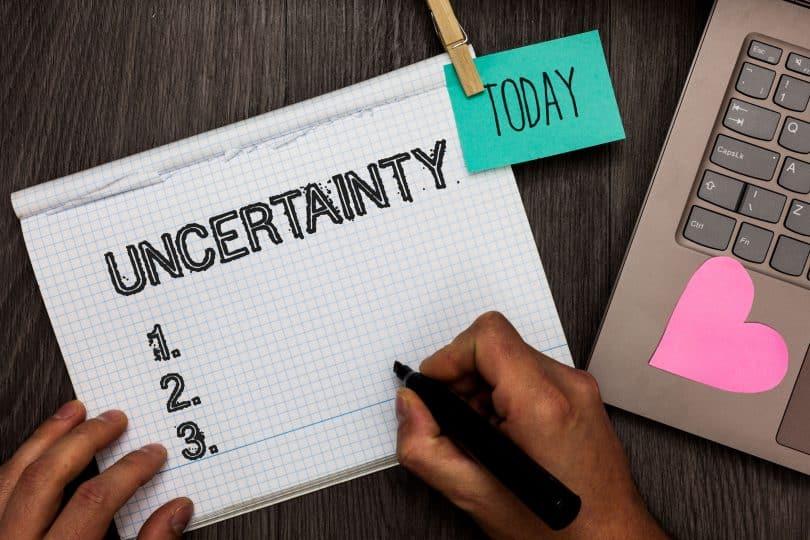 """Caderno com a palavra """"uncertainty"""" e notebook ao lado."""