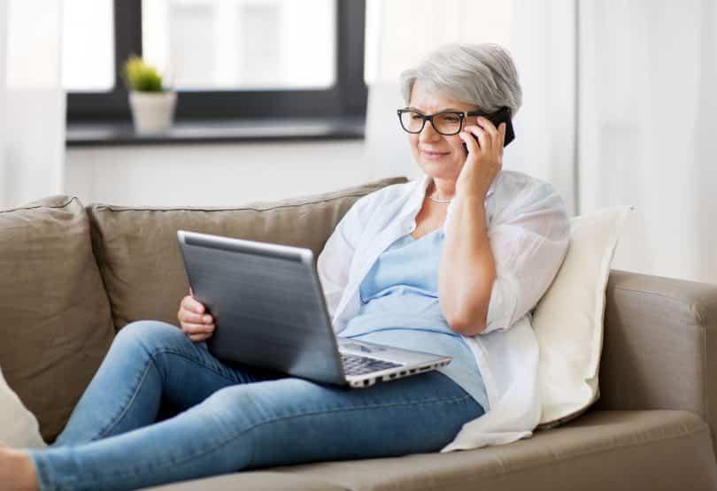 Idosa branca deitada num sofá com computador no colo e celular na orelha.