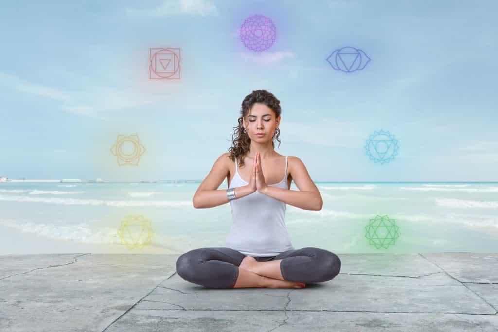 Mulher sentada em posição de lótus com desenhos dos chakras em volta dela.