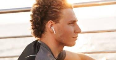 Homem visto de perfil, usando fones de ouvido, com olhar pensativo.