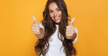 Mulher de cabelos longos e ondulados sorrindo ao levantar seus dedões das mãos para cima.