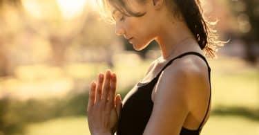 Mulher vista de perfil, com os cabelos presos e roupas de ginástica, junta suas mãos com os olhos fechados.