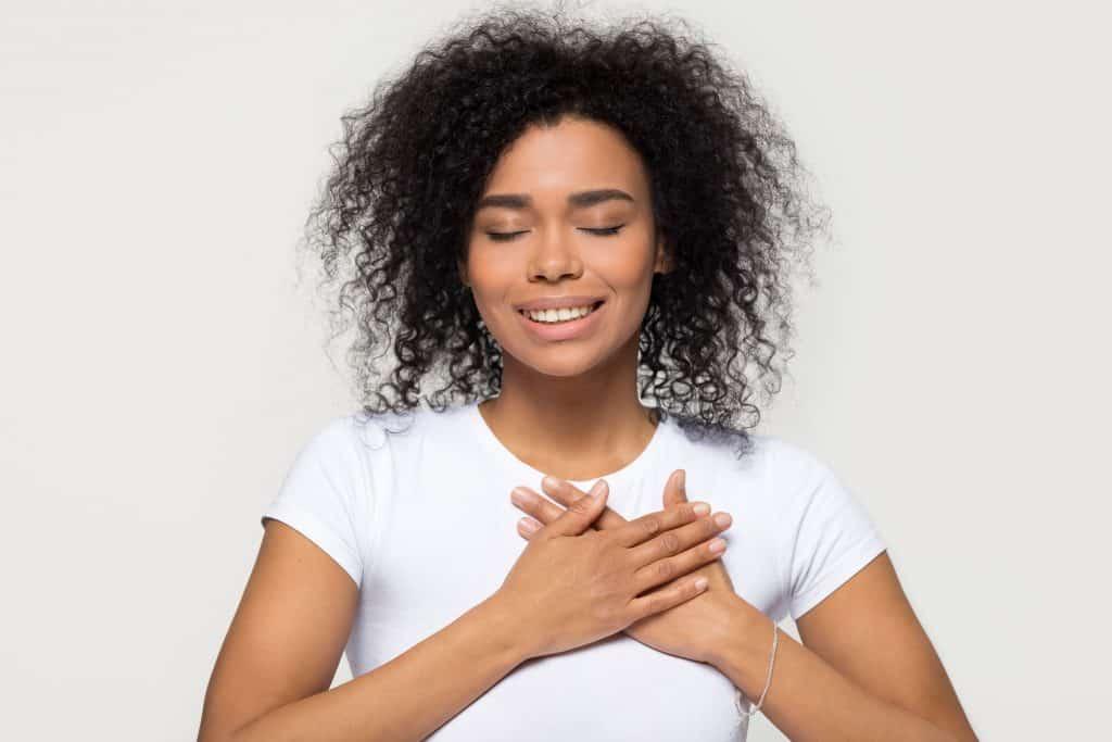 Mulher de cabelos cacheados sorrindo com as mãos sobre o peito.