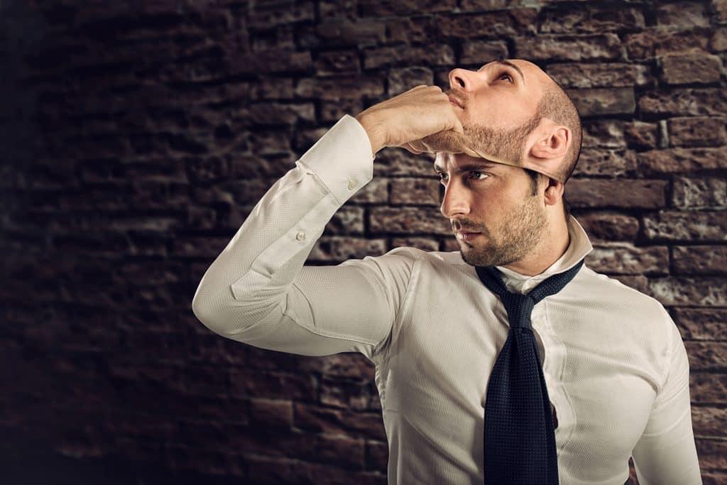 Homem vestido roupas sociais tira de seu rosto uma máscara com sua própria face.