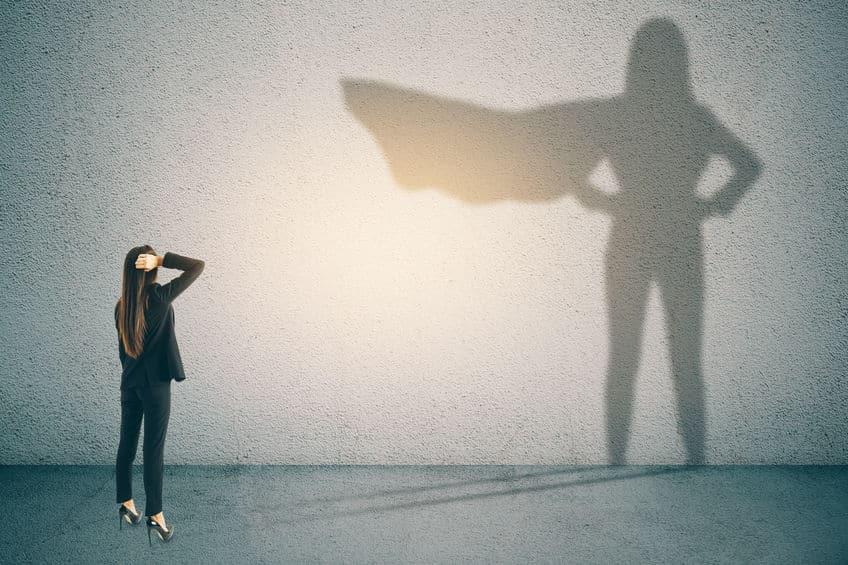 Ilustração de uma mulher olhando para sua sombra em uma parede, que a mostra com uma capa de super-heroína.
