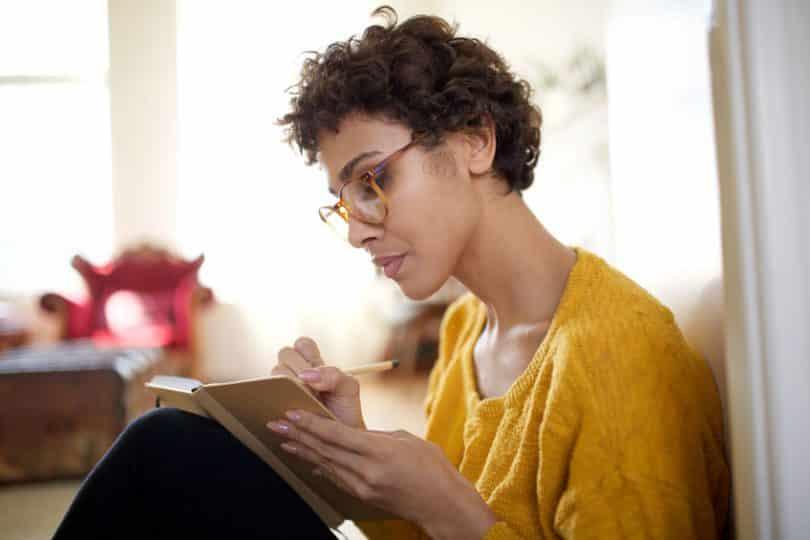 Mulher sentada escrevendo em caderno concentrada