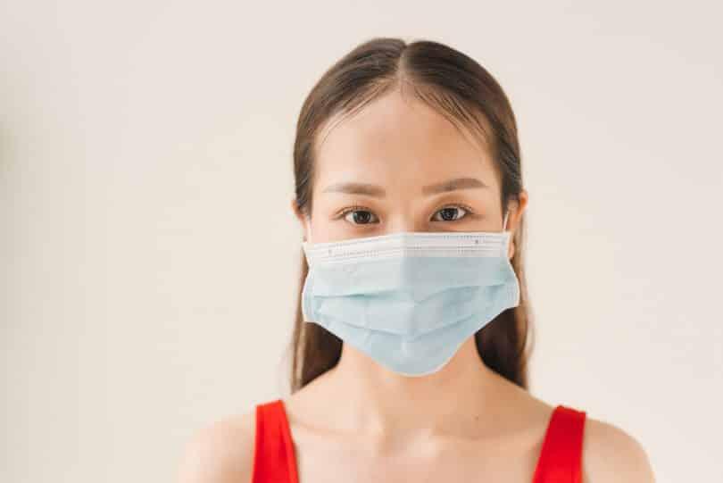 Rosto de uma mulher jovem usando máscara de proteção.