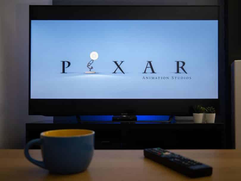 Televisão mostrando a animação da Pixar e na mesa em frente uma xícara e um controle da TV