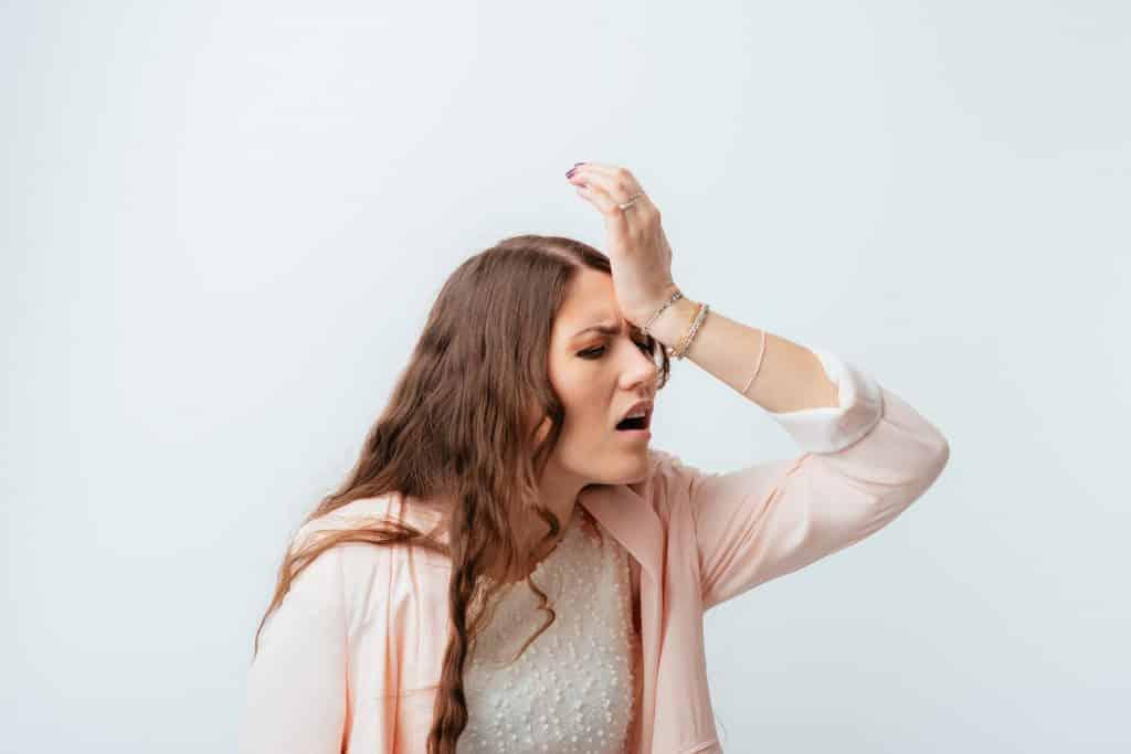 Mulher branca com mão na cabeça e expressão inconformada.