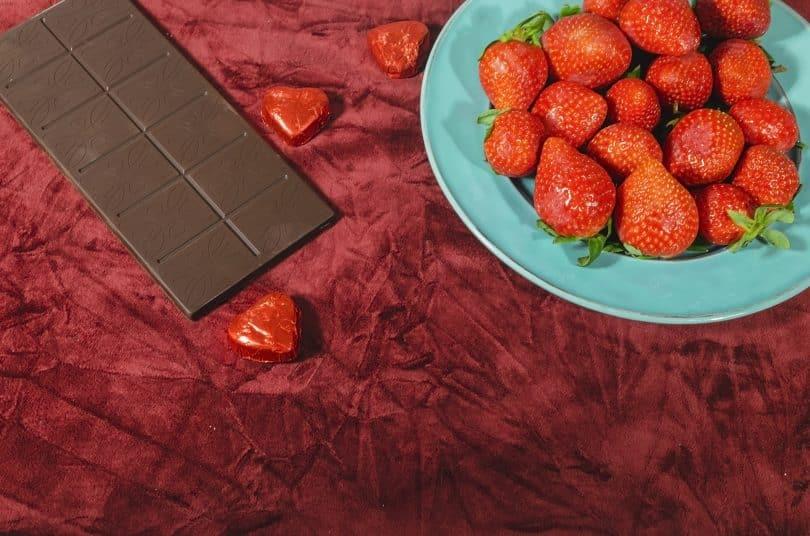 Imagem de um prato com lindos morangos vermelhos e uma barra de chocolate sobre um lindo tecido na cor vermelho. Os alimentos ajudam aumentar a libido.