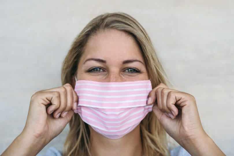 Mulher colocando uma máscara de proteção facial em seu rosto.