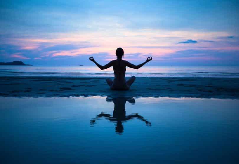 Mulher sentada meditando na praia com céu rosa e azul ao fundo