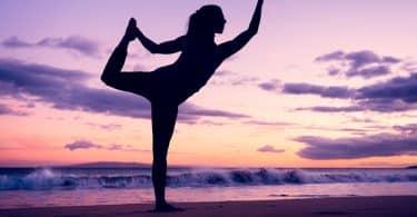 Mulher fazendo ioga numa praia meio a pôr-do-sol.
