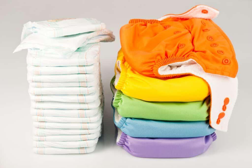 Imagem de duas pilhas de fraldas ecológicas. Uma pilha é de fraldas brancas e a outra é de fraldas coloridas.