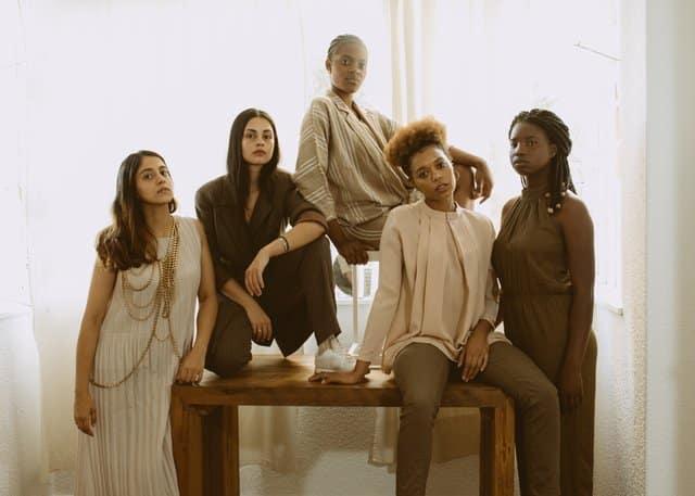 Mulheres pretas e brancas em ensaio fotográfico em mesa de madeira usando roupas com tons parecidos