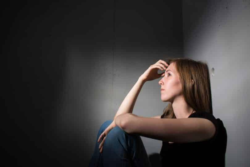 Mulher sentada em quarto escuro, com a mão sobre a testa.