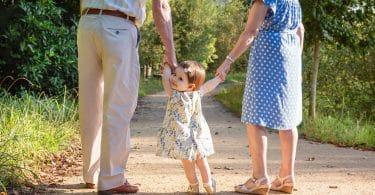 Avô e avó andando de mãos dadas com sua neta pequena, que olha para trás.