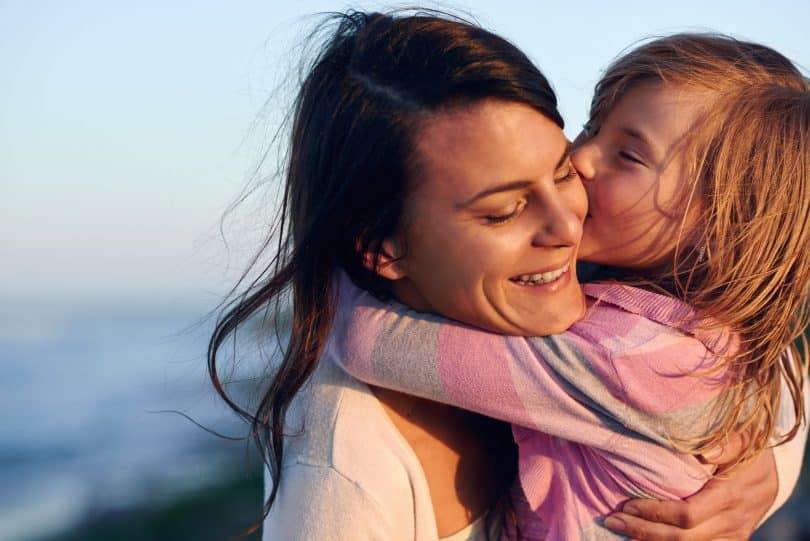 Filha pequena beijando o rosto da mãe, que sorri, em frente à praia.