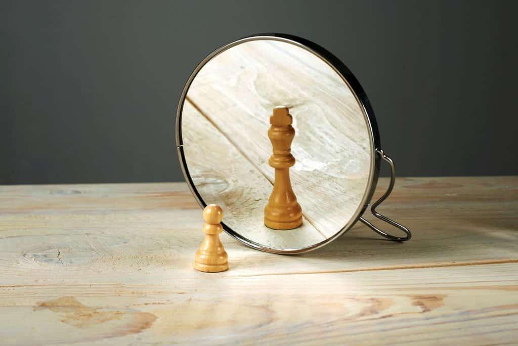 Peão de xadrez refletida no espelho como Rei.