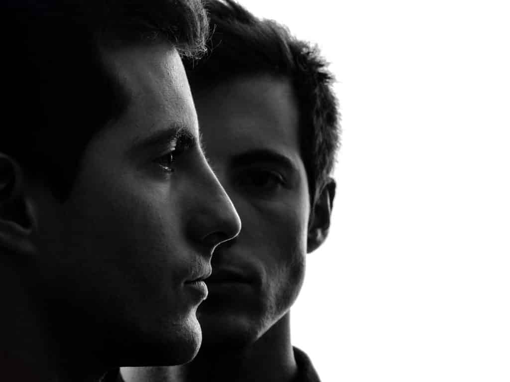 Perfil de dois homens em preto e branco.