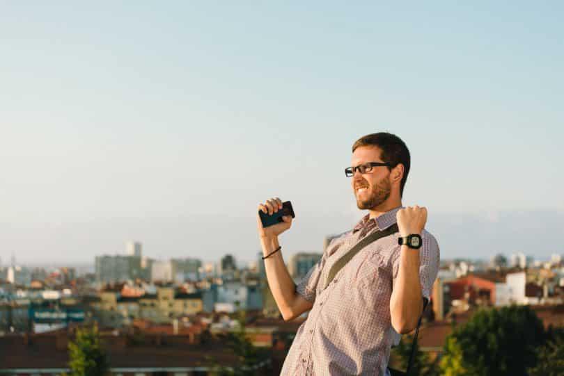 Homem de camisa de botão e óculos com os punhos das mãos para cima, em sinal de vitória.