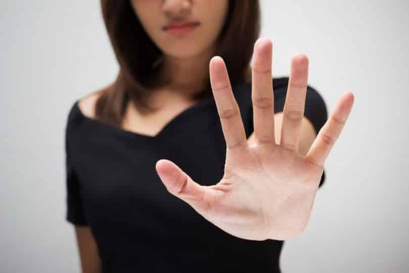 Mulher com mão para frente usando vestido preto