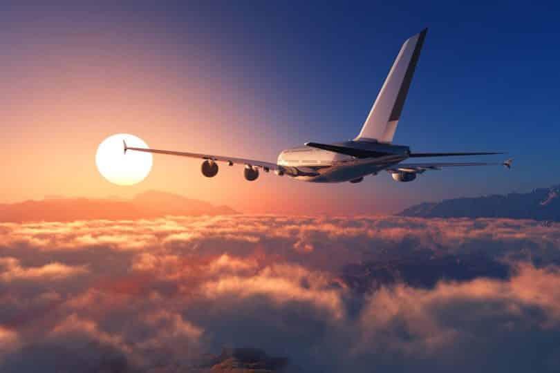 Avião sobrevoando nuvens com sol ao fundo