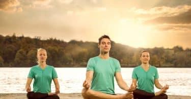 Três pessoas sentadas meditando em frente a um rio.