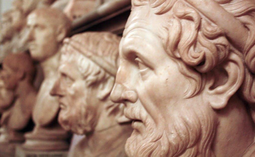 Esculturas esculpidas em mármore de filósofos da Grécia Antiga, vistas de perfil.