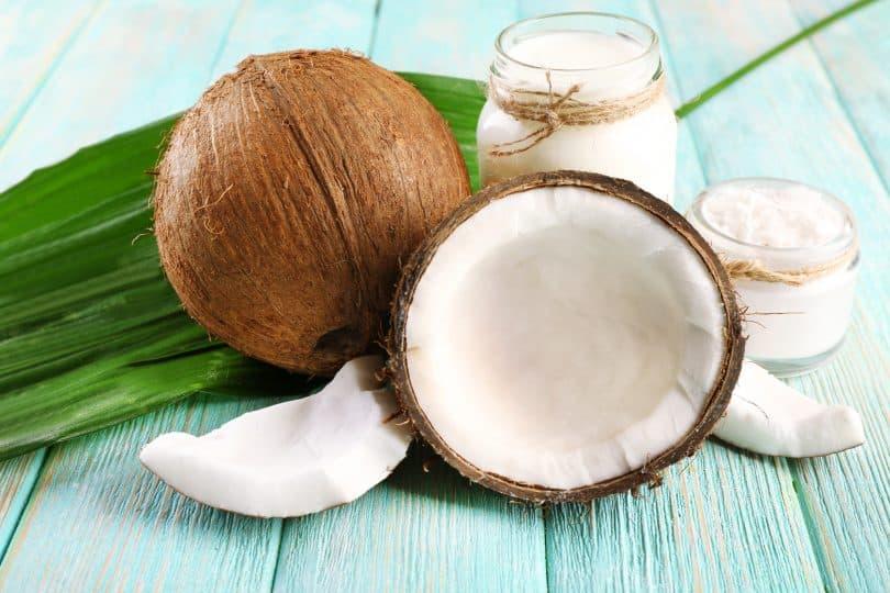 Imagem de metade de um coco e um coco inteiro sobre uma mesa de madeira pintada de azul claro.