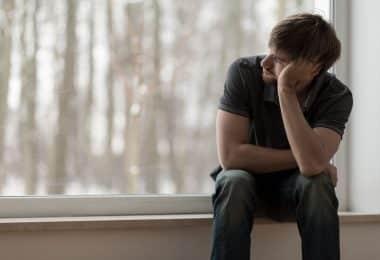 Homem sentado ao lado de uma janela apoiando sua cabeça com seu braço com rosto de tristeza