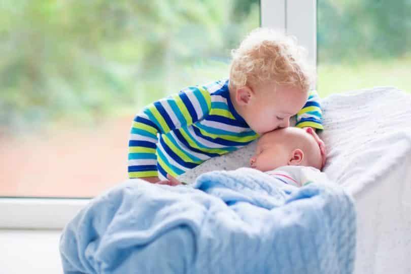 Irmão beijando testa de irmão mais novo dormindo
