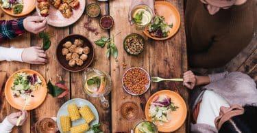 Mesa com pessoas comendo coisas saudáveis.