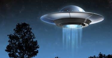 Imagem de uma nave alienígena a noite ao lado de uma árvore.