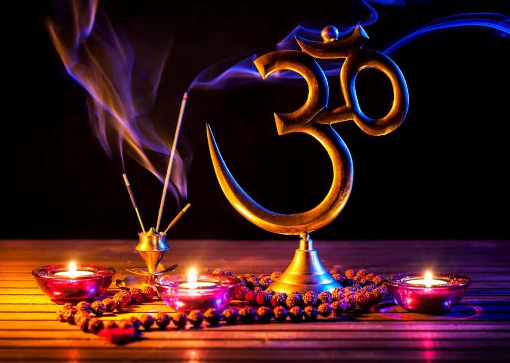 Símbolo OM com incenso e velas do lado