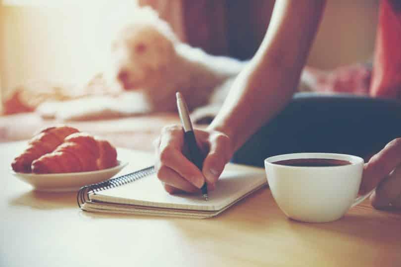 Mulher segurando uma caneta e escrevendo em seu caderno ao lado de uma xícara de café