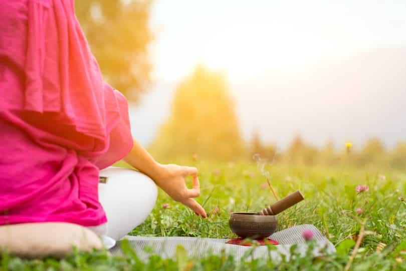 Imagem de um lindo gramado. Nele encontra-se uma mulher sentada em posição de meditação.