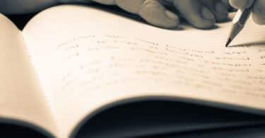 Pessoa escrevendo num caderno